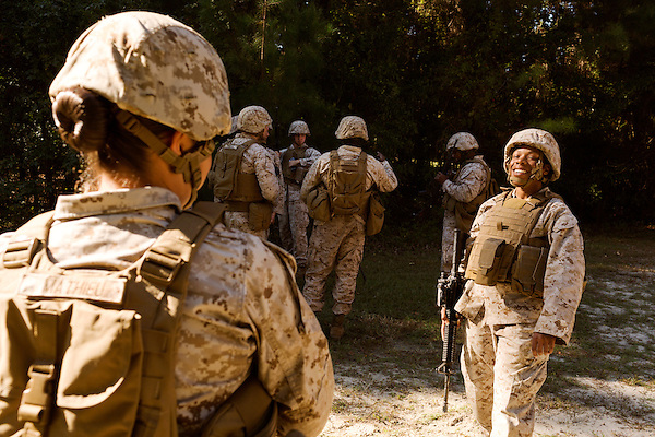 October 23, 2014. Camp LeJeune, North Carolina.<br />  Cpl. Raquel Mathieu, left, and Sgt. Nyree Wilson, right, joke after taking part in rifle training with their infantry fire team. The two Marines have the MOS of Infantry Rifleman (0311), a job previously closed to women.<br />  The Ground Combat Element Integrated Task Force is a battalion level unit created in an effort to assess Marines in a series of physical and medical tests to establish baseline standards as the Corps analyze the best way to possibly integrate female Marines into combat arms occupational specialities, such as infantry personnel, for which they were previously not eligible. The unit will be comprised of approx. 650 Marines in total, with about 400 of those being volunteers, both male and female. <br />  Jeremy M. Lange for the Wall Street Journal<br /> COED