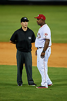 Greeneville Reds manager Gookie Dawkins (9) talks with umpire Caleb Stone during a game against the Pulaski Yankees on July 27, 2018 at Pioneer Park in Tusculum, Tennessee.  Greeneville defeated Pulaski 3-2.  (Mike Janes/Four Seam Images)