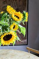 A flower arrangement of bold yellow sunflowers brighten any room.