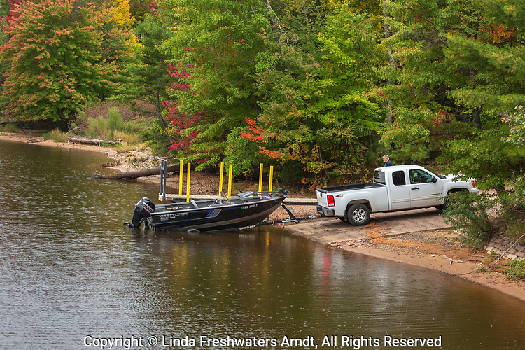 A man pulling his boat out of the Rainbow Flowage after a successful morning of fishing.