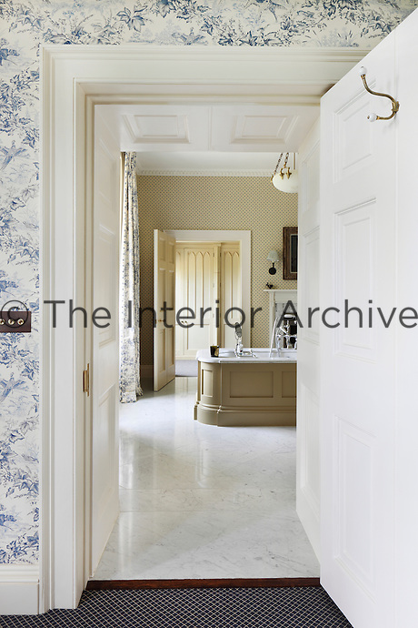 The blue and white hunting themed wallpaper of the bedroom continues in the matching curtains of the ensuite bathroom