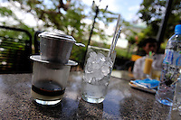 """Ca phe sua da, literally """"coffee milk ice"""", is a unique Vietnamese recipe. Here the hot coffee is dripping through the metal drip filter (ca phe phin) onto condensed milk. The coffee and milk will then be mixed and poured into the glass of ice. Vung Tau, Vietnam"""