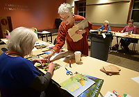 NWA Democrat-Gazette/ANDY SHUPE<br /> Nancy Hartney (center) of Fayetteville speaks Wednesday, Jan. 10, 2018, with Linda Ratzlaff of Fayetteville as she makes an envelope during a stationary-making workshop at the Fayetteville Public Library.