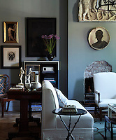 In the living room, the sofa is a custom design, the side table is by Herve Van der Straeten, and the plaster frieze and portrait below it are 19th-century French