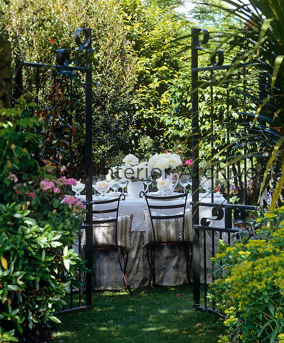 Open wrought iron gate leading to a secret dining area in the garden