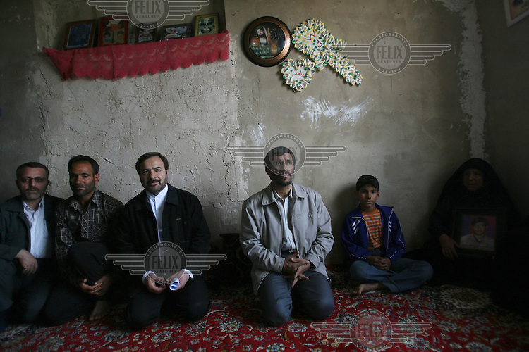 Iranian President Mahmoud Ahmadinejad kneels on the floor with the family of a soldier killed during the Iran-Iraq War. The Iranian President visits these families as part of the programme of one of his regional tours.