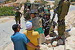 An Israeli soldier uses a riot shield to force back Palestinian protesters as they attempt to pass  a road block during a demonstration against Israel's controversial separation barrier in the West Bank town of Beit Jala near Bethlehem on 04/07/2010.