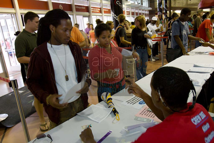 """Morehouse senior Amir Bellamy (left) and his girlfriend, Kalinda Campbell, speak with a production assistant at the Georgia Dome in Atlanta on Sunday during registration to audition for the hit television show """"American Idol."""" Tryouts will be held on Tuesday at the Dome."""