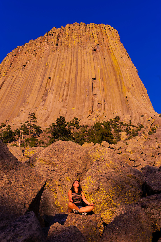 Teenaged girl doing yoga in front of the 867 foot tall Devils Tower (a granite monolith which is a sacred site to American Indians), Devils Tower National Monument, Wyoming USA