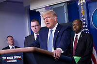 Pete Gaynor, Administrator, Federal Emergency Management Agency (FEMA), left, and United States Secretary of Housing and Urban Development (HUD) Ben Carson, right listen as United States President Donald J. Trump makes remarks on the Coronavirus crisis in the Brady Press Briefing Room of the White House in Washington, DC on Saturday, March 21, 2020.  Credit: Stefani Reynolds / Pool via CNP/AdMedia