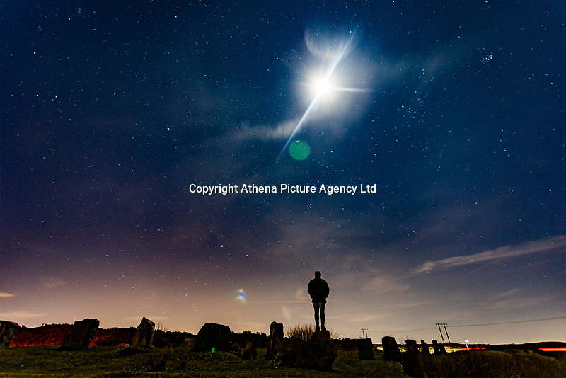 A silhouette of a man under a half moon and stars visible over Keepers Pond, Pontypool, Wales, UK.<br /> Re: Below zero temperatures have hit most parts of the UK this month. This month will also have no full moon, a rare phenomenon which only happens during the month February and is known as Black Moon with January and March experiencing Blue Moons.