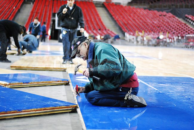 Kentucky Exposition Center staff member tightens the bolt that hold each plank of the basketball court together at Freedom Hall on Monday December 5, 2010. Photo by Ryan Buckler | Staff