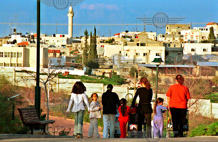 Mothers and their children hang out in the streets of the Israeli settlement of Matan, next to the West Bank Palestinian village of Chabla..A concrete separation wall was built six years ago between the two settlements, as part of an Israeli plan to separate Israeli and Palestinian populations.