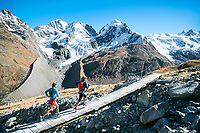 Trail running across a bridge above the Rosegtal with Piz Bernina and Piz Roseg in the background. Pontresina, Switzerland