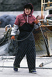A woman helps her husband readies their nets for the next day of fishing off the Strait of Tsugaru in the fishing port town of Omma, on the Northern most tip of Honshu, Japan. (Jim Bryant Photo)