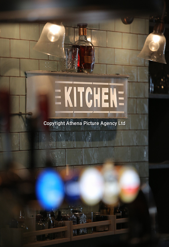 An illuminated Kitchen sign behind a bar