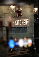 An illuminated Kitchen sign behind a bar