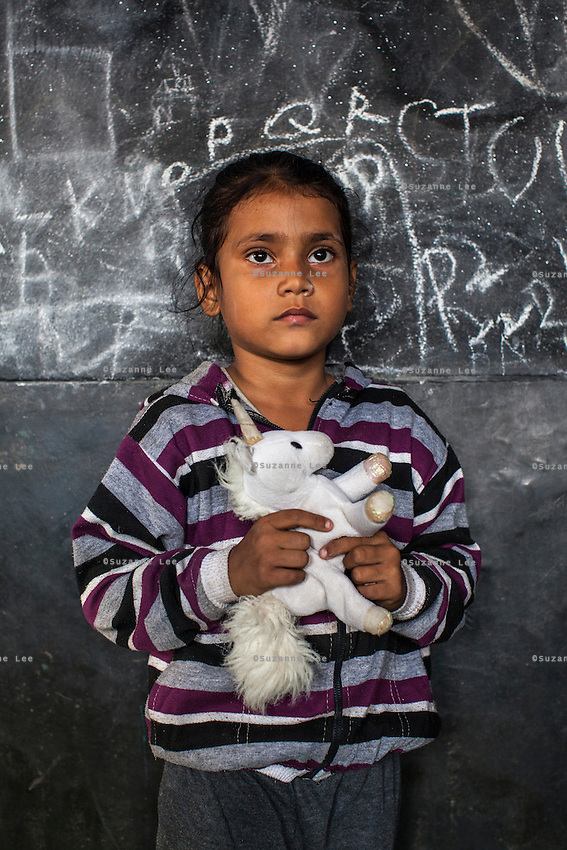 Anya, 7, poses for a portrait with a soft toy in the Guria Non-Formal Education center in the middle of the Shivdaspur red light district, Varanasi, Uttar Pradesh, India on 20 November 2013. Guria uses the soft toys as a form of therapy for the children of the women in prostitution and also use it as signals of the children's emotional wellbeing.