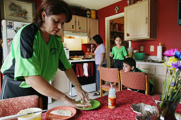 (MODEL RELEASED IMAGE). After the Saturday soccer game, Diana and Alejandrina perform a family ritual: making fresh tortillas (in background) for cheese quesadillas. Hungry Planet: What the World Eats (p. 273). The Fernandez family of San Antonio, Texas, is one of the thirty families featured, with a weeks' worth of food, in the book Hungry Planet: What the World Eats.
