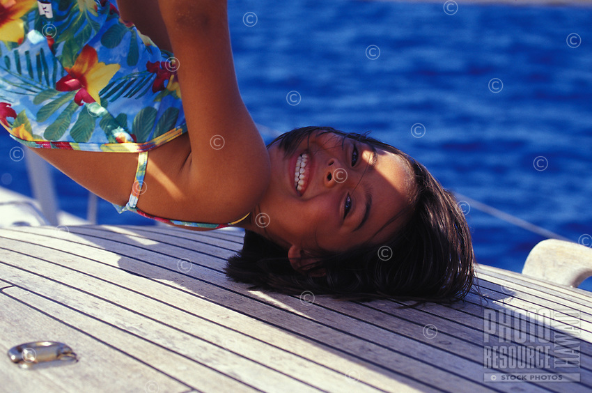 Young girl on vacation on a sailboat, Tahiti, French Polynesia