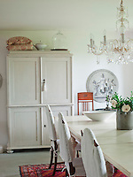 These dining chairs have been covered in a linen fabric that belonged to the owner's grandmother; a focus on materials and furniture that have personal meaning is apparent throughout the house