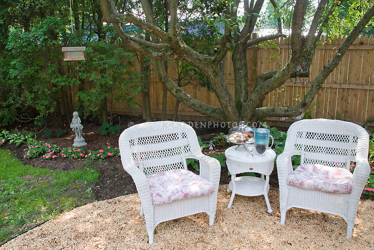 Backyard stone pebble mulch patio in circular pattern, with wood privacy fence, shade trees, lawn grass, impatiens, bird feeder, white wicker furniture table and armchairs, dining outdoors in summer