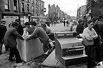 Toxteth, Liverpool. 1981<br /> Local men helping them selves from burnt out shops attacked by rioters during the previous night.