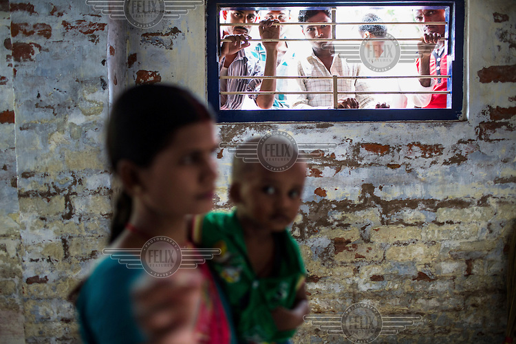 Men look in through a window while a woman and her child wait for their turn to be seen at the general outpatients department of the Duncan Hospital.
