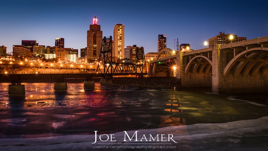 Ice covered Mississippi River and St. Paul skyline with railroad bridge and Roberts Street bridge at dusk.