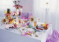 A dining table is laid for Christmas with white tableware, star decorations, lit candles and wine glasses.