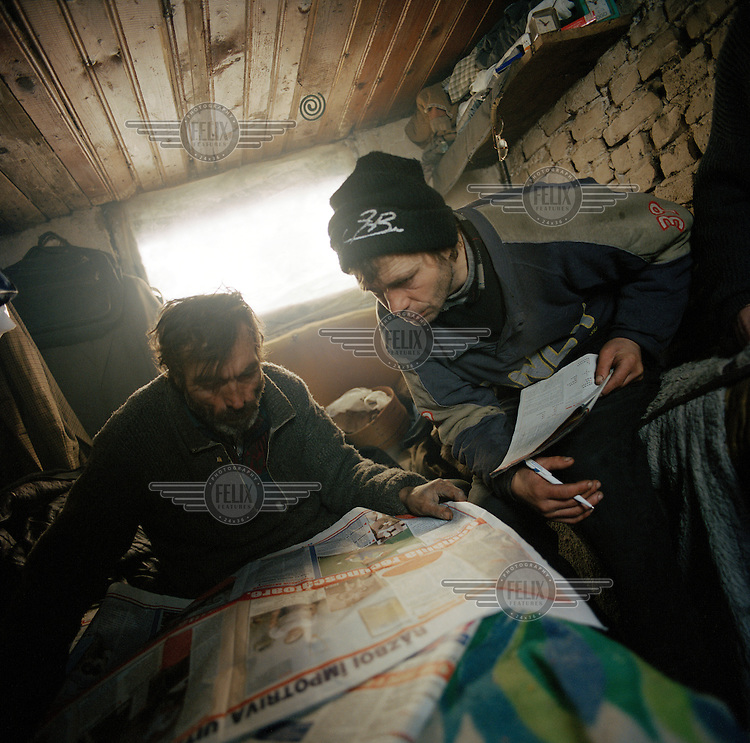Gheo and Vasille reading the newspaper..In Calea Vacaresti, south east of the capital, four families have made their homes in the dried out basin of an artificial lake, constructing shacks from bricks, plastic and assorted rubbish.