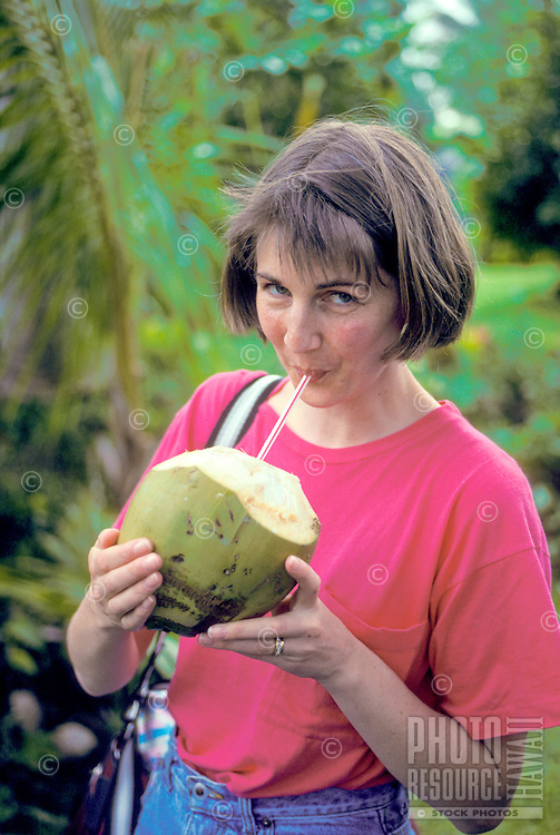 Woman on vacation drinking from a coconut
