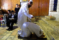 "An ultra-Orthodox Jew bows down as he is symbolically beaten during the ""Malkot"" ceremony in a covered section of the Western Wall in Jerusalem's Old City shortly before the start of Yom Kippur September 15, 2002 in Jerusalem, Israel. The ceremony represents punishment for sins and is performed while reciting prayers for forgiveness ahead of Judaism's holiest day, the Day of Atonement, which begins at sunset on Sunday September 15 and ends at the same time the following evening."