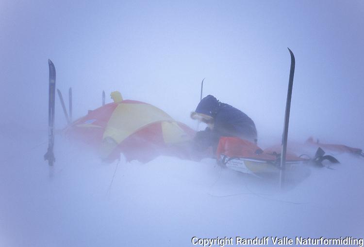 Mann og telt i snøstorm. ---- Man and tent i snow storm.