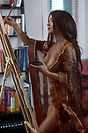 Beautiful young woman sumi-e artist with an easel painting half nude in comfort of her home studio wearing just a sheer robe over her naked body