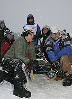 Saturday February 25, 2006 Willow, Alaska.  Volunteers hold a sled back at the start day of the Junior Iditarod sled dog race.  Willow Lake.