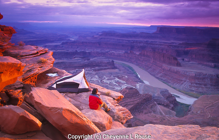 Camper at inspirational Dead Horse Point - I am NOT condoning this action - it was set up for a stock photo - camping is NOT allowed on this ledge. <br /> Dead Horse Point State Park, Utah.