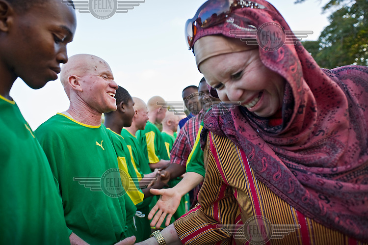 Madame Al-Shaymaa J. Kwegyir (right) visits a football club in Dar es Salaam where she is congratulating a team for their success as well as their integration of albinos. Kwegyir is Tanzania's first albino Member of Parliament. The nomination of an albino MP is a first step in the fight against the widespread belief that albinism is the result of a curse. Discrimination against albinos is a serious problem throughout sub-Saharan Africa, but recently in Tanzania albinos have been killed and mutilated, victims of a growing criminal trade in albino body parts fuelled by superstition and greed. Limbs, skin, hair, genitals and blood are believed by witch doctors to bring good luck, and are sold to clients for large sums of money, carrying with them the promise of instant wealth.