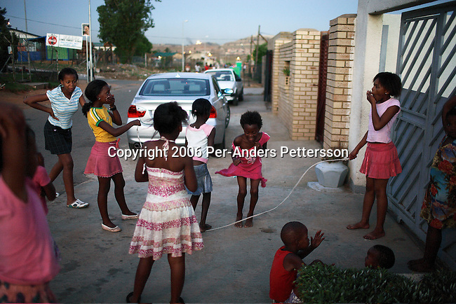 SOWETO, SOUTH AFRICA OCTOBER 24: Children play in the street as the sun goes down October 24, 2006 in the Orlando West section of Soweto, Johannesburg, South Africa. Soweto is South Africa?s largest township and it was founded about one hundred years to make housing available for black people south west of downtown Johannesburg. The estimated population is between 2-3 million. Many key events during the Apartheid struggle unfolded here, and the most known is the student uprisings in June 1976, where thousands of students took to the streets to protest after being forced to study the Afrikaans language at school. Soweto today is a mix of old housing and newly constructed townhouses. A new hungry black middle-class is growing steadily. Many residents work in Johannesburg but the last years many shopping malls have been built, and people are starting to spend their money in Soweto.  .(Photo by Per-Anders Pettersson/Getty Images)..