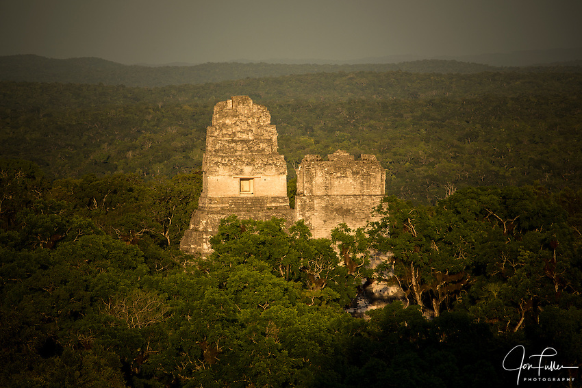 View at sunset of Temples I and II from Temple IV in the Mayan archeological site of Tikal National Park, Guatemala.  The shadow of Temple IV is in the forground.  A UNESCO World Heritage site since 1979.