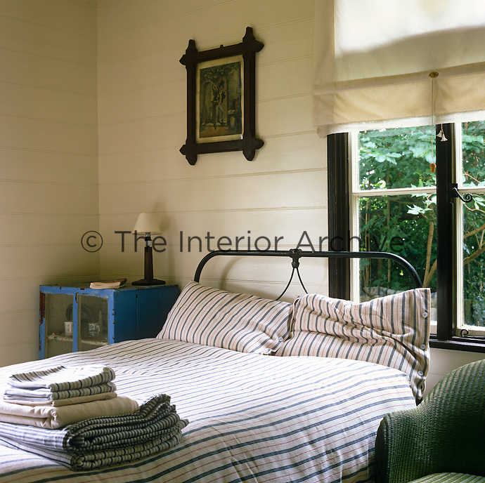 A simple wrought-iron bed  has been covered in fresh striped bedlinen