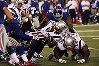 DE Matt Broha und DT Markus Kuhn (Giants) stoppen RB Brandon Bolden (Patriots)