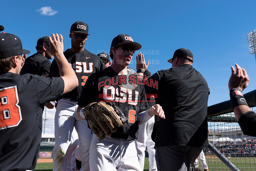 Oregon State Beavers left fielder Joe Casey (6) is high-fived by teammates and coaches between innings of a game against the Gonzaga Bulldogs on February 16, 2019 at Surprise Stadium in Surprise, Arizona. Oregon State defeated Gonzaga 9-3. (Zachary Lucy/Four Seam Images)
