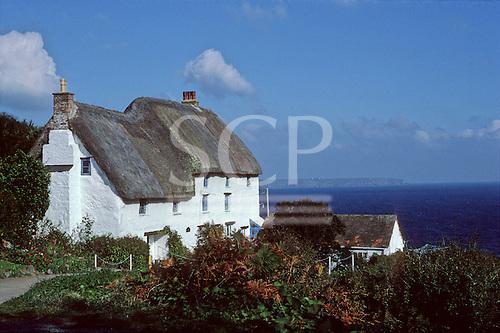 Cornwall, England. Typical thatched, whitewashed Cornish cottages with the sea beyond.