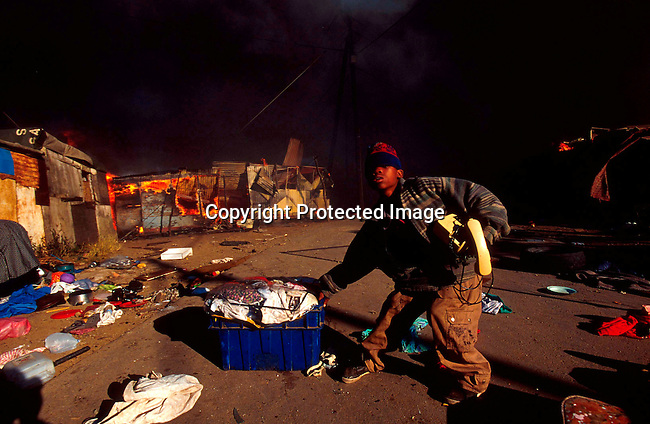 DIENVFI00062.Enviroment. Fire.An unidentified boy is trying to save some of his families belongings as a shack fire is raging on July 6, 2001, in Duncan Village, a poor township outside East London in Eastern Cape province, South Africa. Eastern Cape is the poorest province in South Africa. Shack fires are very common as the shacks are built very close to each other and people are using paraffin stoves which easily fall over and the fires spread quickly. South Africa is facing a severe backlog of housing for the poor. The ANC government promised to build 1 million houses during the first democratic election in 1994..©Per-Anders Pettersson/iAfrika Photos