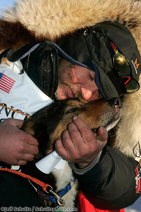 Wednesday March 14, 2007   ----   Norwegian musher Robert Sorlie gives one of his lead dogs a hug shortly after he arrived in Nome to take a 13th place finish.