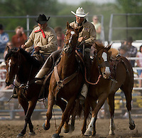 Stephen Brashear.A pair of pick up men lead a saddle bronc back to the the chutes during the Miles City Bucking Horse Sale at the Eastern Montana Fairgrounds in Miles City Montana Sat., May 19, 2007. Saddle broncs and bareback broncs are auctioned off after they are bucked.