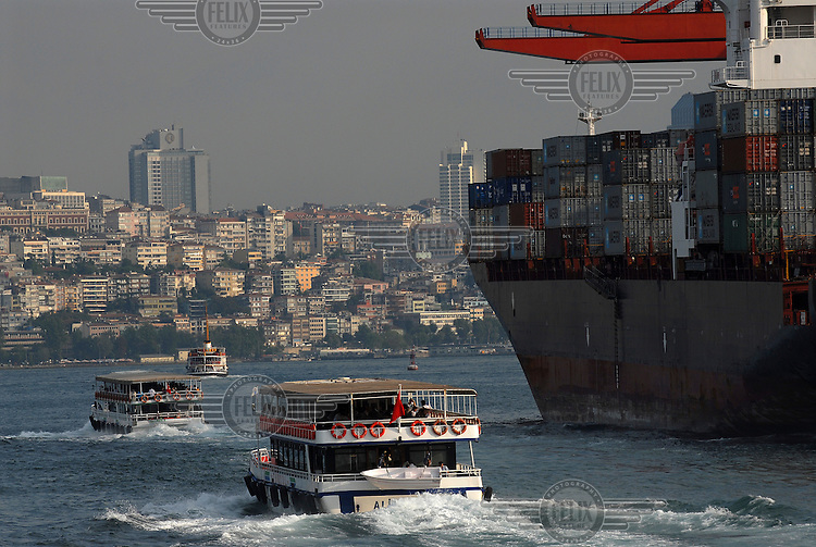 Commuter ferries passing a cargo container ship in the Bosphorus.