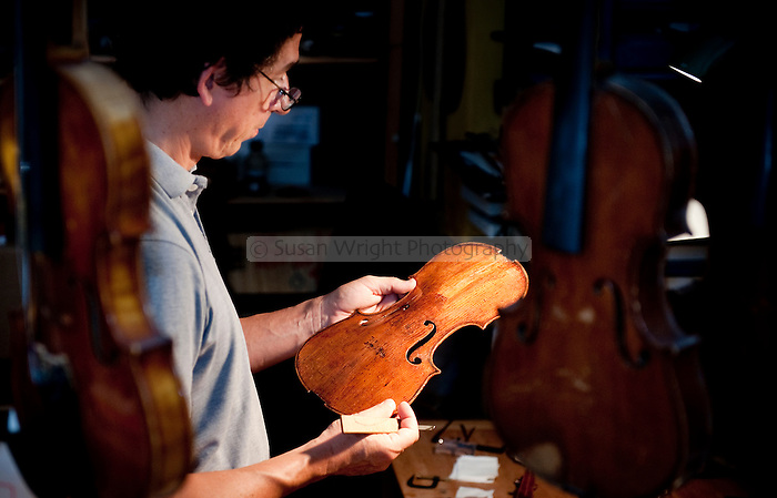 Aldo Santini, artisan violin maker and restorer (liutaio) examines the restoration work of a 17th century violin, in his workshop (bottega) on Via dei Velluti in Florence, Italy