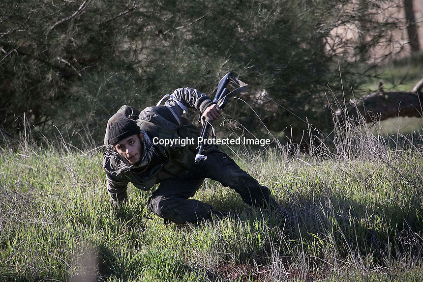 In this Saturday, Dec. 15, 2012 photo, a Syrian rebel fighter takes cover as during heavy clashes inside one militar academy besieged by rebels at the north of Aleppo, Syria. The Free Syrian Army took control over the Academy after several hours battling the troops loyal to President Bashar al-Assad. Among the casualities are one FSA General and one Syrian journalist. (AP Photo/Narciso Contreras)